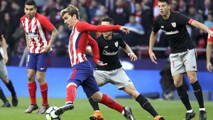 Griezmann controla el balón ante dos rivales del Athletic