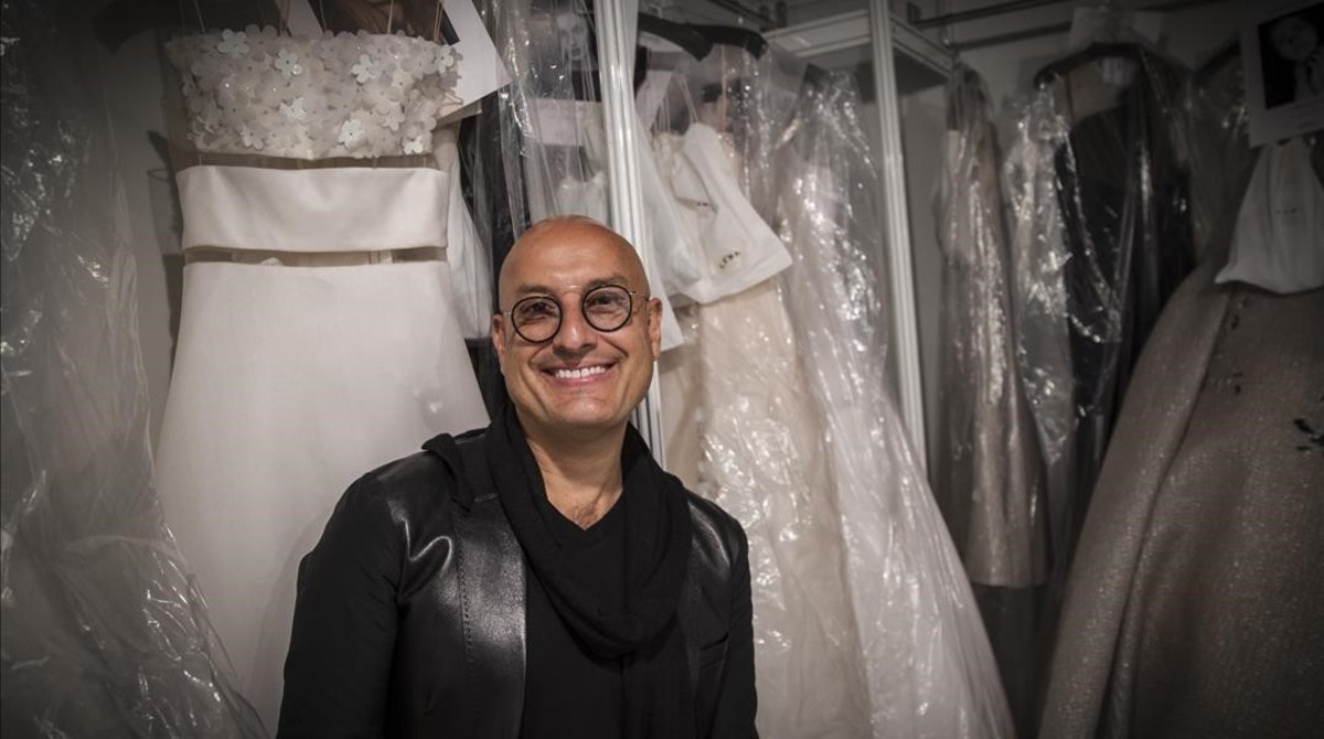 El diseñador venezolano Ángel Sánchez posa entre sus diseños de moda nupcial y fiesta.