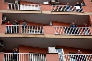 GRAF3230. L'HOSPITALET DE LLOBREGAT (BARCELONA), 29/03/2020.- Vecinos de L'Hospitalet salen a sus balcones como cada día a animar y homenajear a los sanitarios, cuando se cumple el decimoquinto día del estado de alarma decretado por el Gobierno por la pandemia de coronavirus. EFE/Toni Albir
