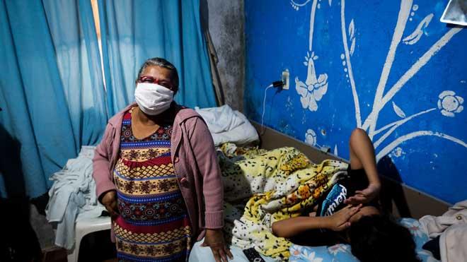 Bolsonaro se desvincula del aumento de muertes por coronavirus en Brasil. En la foto,Maria Niva, de 63 años, junto a su nieta enferma en su casa en el barrio de Chácara Três Meninas, en la región metropolitana de Sao Paulo.