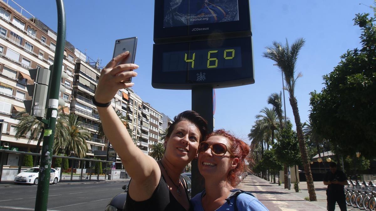 Unas mujeres se hacen un 'selfie' ante un termómetro callejero en Córdoba, en una imagen de archivo.