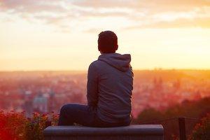 Un chico mira el amanecer.