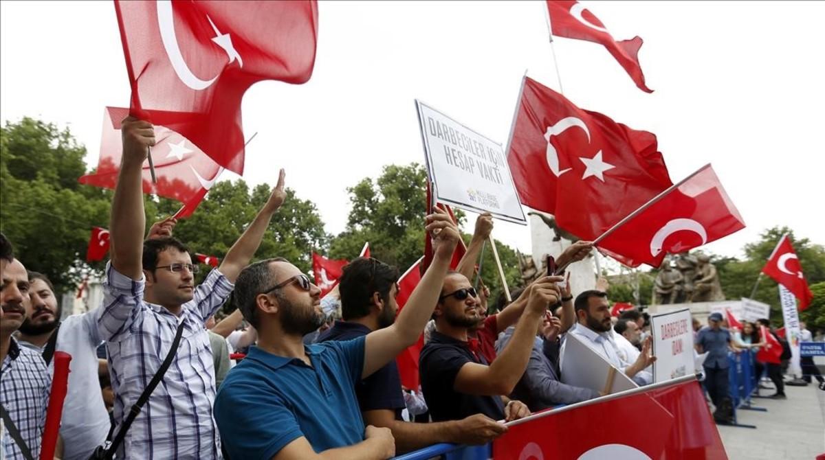 Ciudadanos turcos ondean banderas de su país durante una protesta en la víspera del primer aniversario del fallido golpe de Estado.