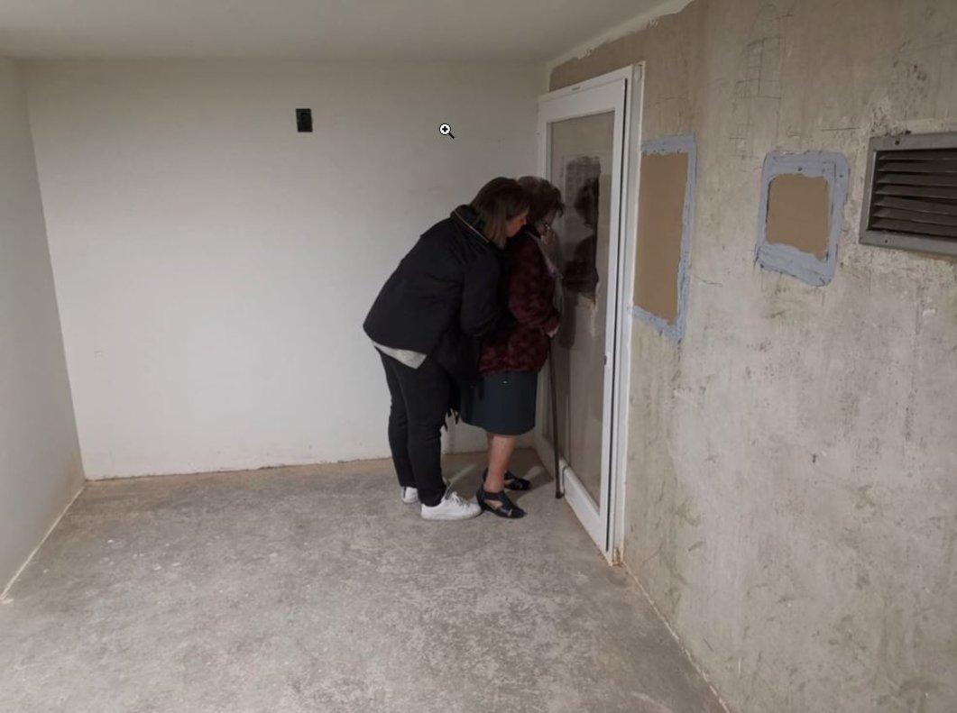 Emocionadas, dos familiares se asoman al agujero practicado en la pared de la cripta del Valle de los Caídos.