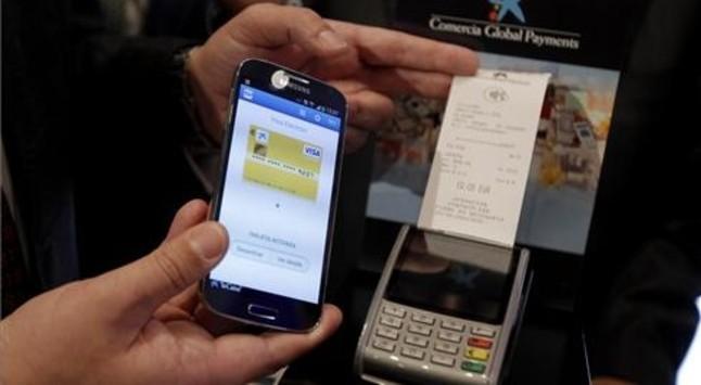 Exemple de pagament amb el mòbil i un datàfon de La Caixa.