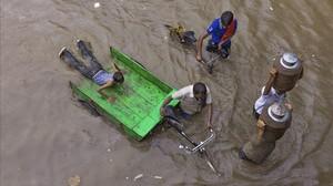 Lecheros intentan abrirse paso por una calle inundada tras las fuertes lluvias en Allahabad, India.