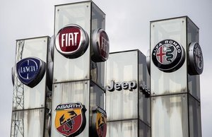 Logotipos demarcas de automóvilesde la empresa Fiat Chrysler Automobiles (FCA) en un concesionario de Turín.