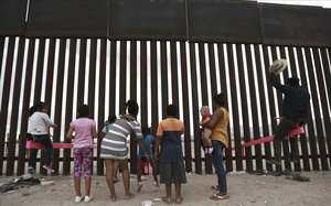 Niños migrantes jugan ante el muro que divide la frontera entre EEUU y México, en Ciudad Juárez.