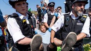 La policía detiene a un activista de 'Extinction Rebellion' que estaba bloqueando este domingo el puente deWaterloo en Londres.