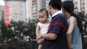 Una pareja pasea por un parque de Shangái con su bebé.