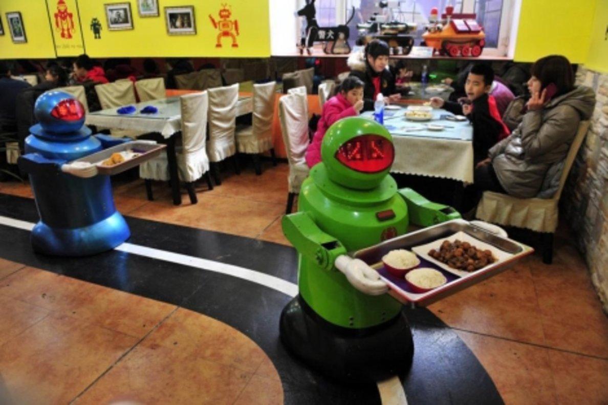 Imagen de archivo de unos robots sirviendo mesas en un restaurante.