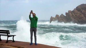 Un hombre se fotografía con fuerte mar de fondo en la Bahía de Fornells,en el municipio de Es Mercadal de Menorca