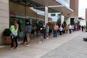 Una larga cola de clientes espera para entrar en una tienda del Viladecans The Style Outlets este lunes