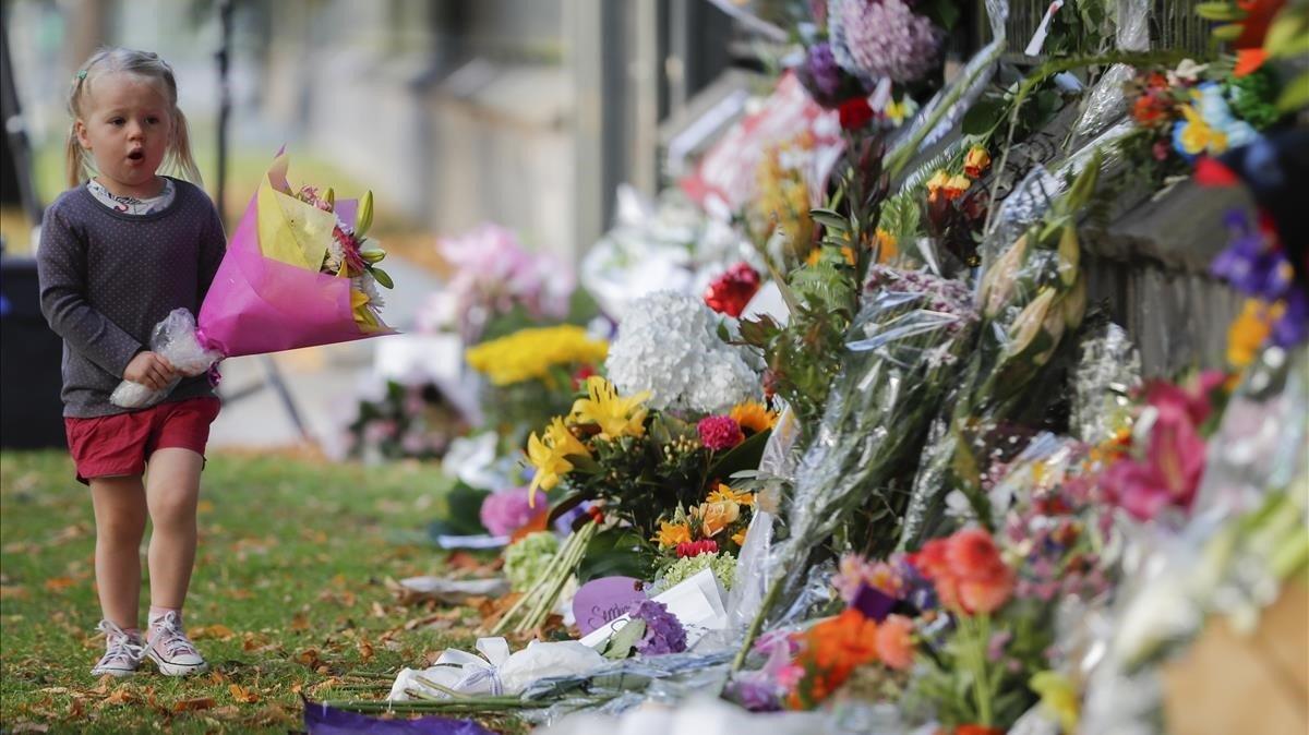 Una niña pone flores en el memorial de recuerdo del atentado en Christchurch, el pasado mes de marzo.