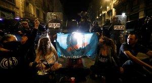 Varios policías vigilan a un grupo de jóvenes sentados en la calzada para protestar contra la sentencia, este sábado en el centro de Barcelona.