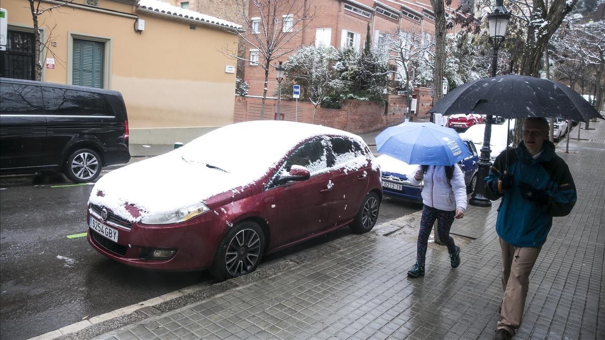 Vehículos embranquecidos por la nieve en la calle Olot, Barcelona.