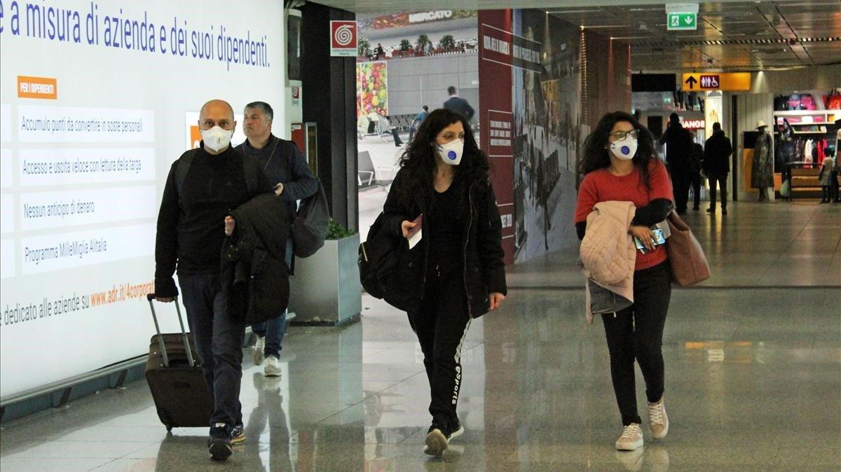 Viajeros con máscaras puestas pasean por el aeropuerto Leonardo da Vinci de Fiumicino, en Roma, el pasado 10 de marzo.