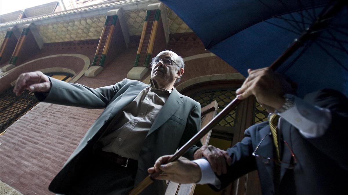 Fèlix Millet saliendo del Palau, intentando taparse con un paraguas, el 23 de julio del 2009, tras la entrada de losMossos.