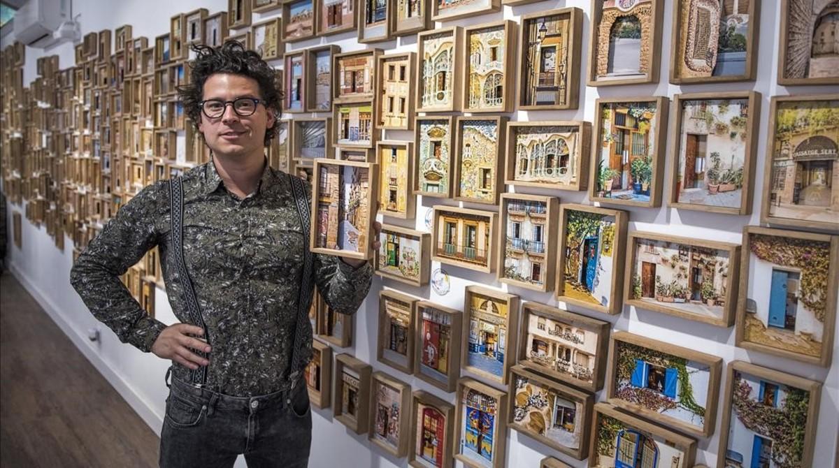 Maxó Rennella, en un rincón de la galería que regenta en Portal Nou con algunas de sus imágenes tridimensionales sobre Barcelona en la pared.