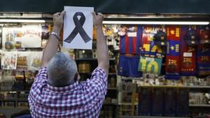 Un quiosquer a la Rambla posa un llaç negre en record de les víctimes.