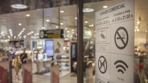 Cartel con el nuevo horario comercial en una tienda de Barcelona.