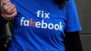 Una mujer lleva una camiseta en contra de la divulgación de noticias falsas a través de Facebook.