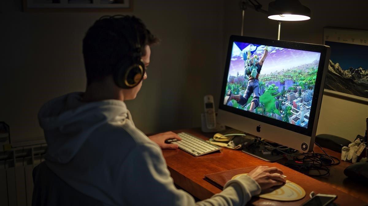 Un niño juega al Fortnite con su ordenador.