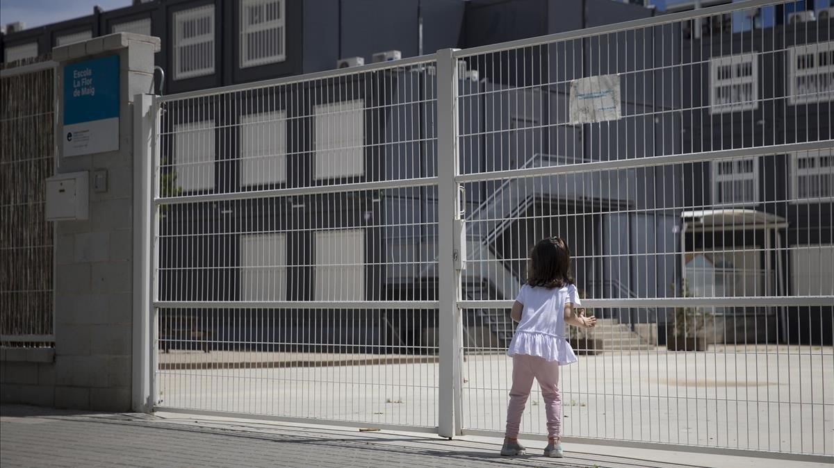 Una niña, frente a la escuela cerrada Flor de Maig, en el Poblenou de Barcelona.