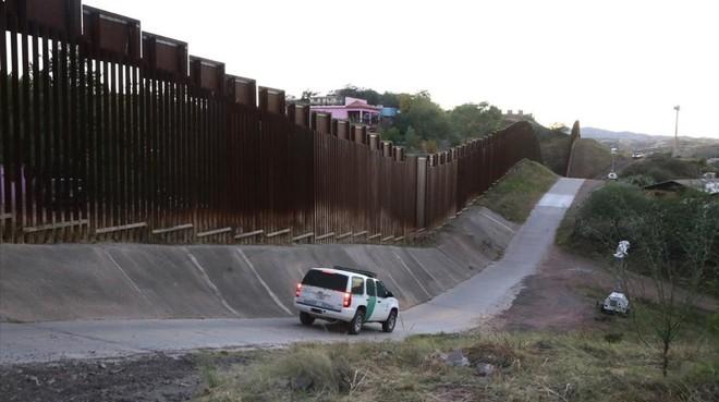 Un coche de la Patrulla Fronteriza de EEUU peina la valla de casi cinco metros que separa buena de los dos Nogales, el estadounidense y el mexicano.