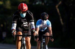 Dos ciclistas practican su deporte por una carretera cercana a Valencia.