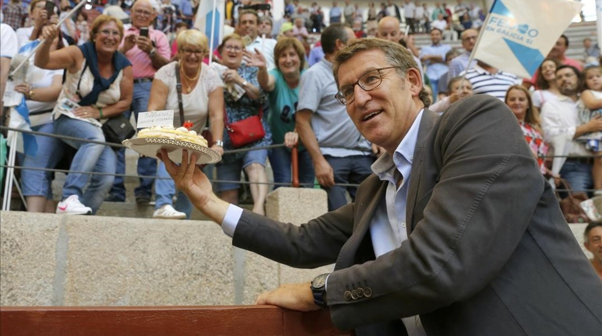 Alberto Núñez Feijóo saluda a varios simpatizantesque le regalaron una tarta por su cumpleaños, durante la campaña cara a las elecciones gallegas.