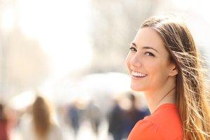 Chica joven sonriendo en la calle.