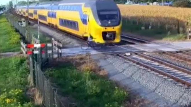 Un ciclista se libra por milésimas de segundo de ser atropellado por un tren en un paso a nivel .