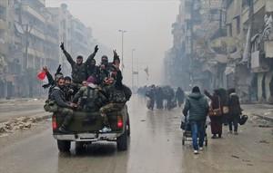 Combatientes progubernamentales hacen la señal de la victoria, ayer en una calle de Alepo.