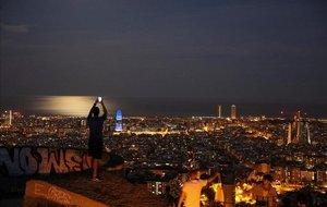 Un chico toma una foto de Barcelona, al anochecer.
