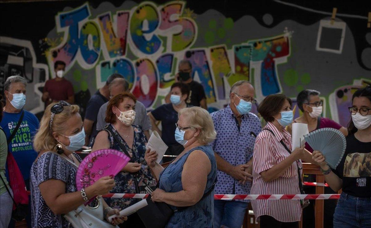 Gente con mascarilla espera para hacerse una prueba PCR en Vilafranca del Penedès.