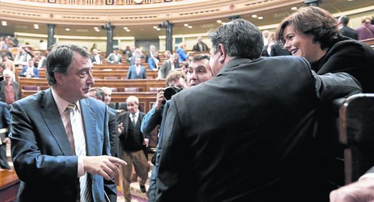 El diputado del PNV Aitor Esteban (izquierda) saluda a Soraya Sáenz de Santamaría, en unpleno del Congreso.