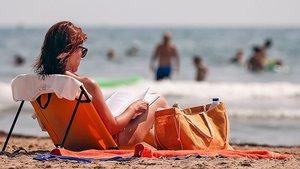 Una mujer lee en una playa de la Comunidad Valenciana.