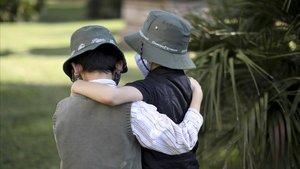 Dos niños con máscarilla, en un parque.