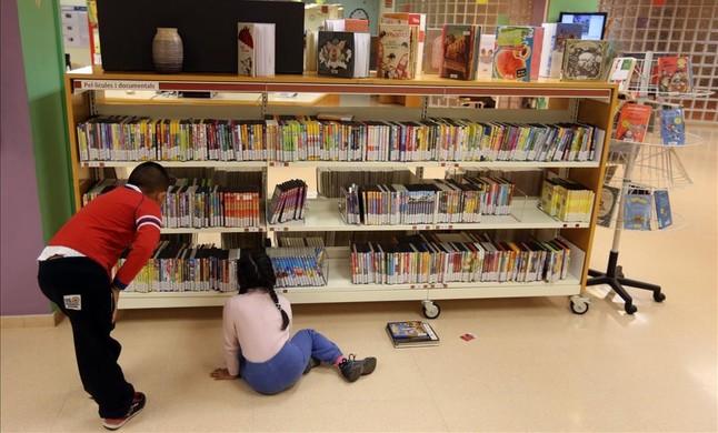 Dos niños consultan libros disponibles en la Biblioteca Central de Cornellà.