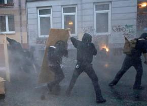 Los manifestantes intentan esquivar los cañones de agua de la policía.