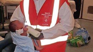 Una asistentaalimentaa un bebétras ser rescatadoen el Mar Mediterraneo.