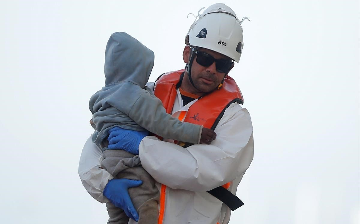 Un sanitario lleva en brazos a un bebé rescatado en una patera, en Málaga.