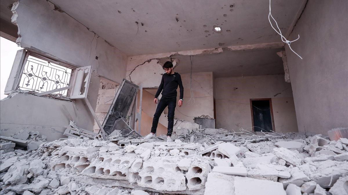 Un joven sirio camina por un edificio derrumbado por bombardeos de Damasco en el noroeste de Idleb, este lunes.
