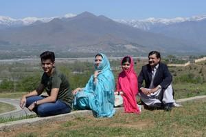 Malala posa junto a sus padres y su hermano en su localidad natal, Mingora (Pakistán), este sábado.