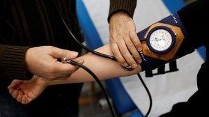 Un médico toma la presión a un paciente.