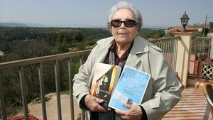 Neus Català sostiene, en el 2012, ejemplares del libro'Un cel de plom' / 'Cenizas en el cielo'.