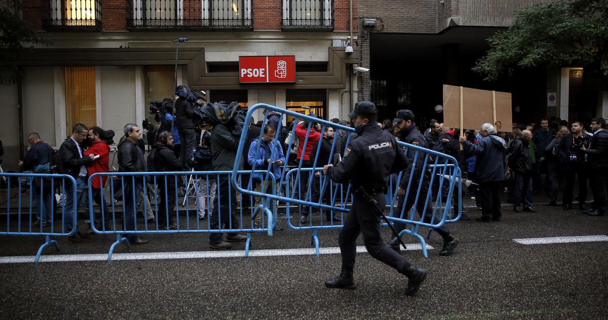 Periodistas, policías y decenas de simpatizantes, ante la sede del PSOE en Madrid.