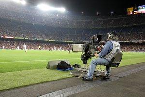 Un reportero gráfico grabando un partido de fútbol.