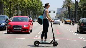 Una mujer circula por Barcelona en patinete eléctrico, este verano.